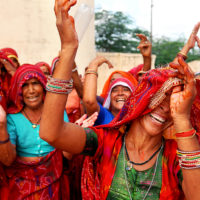 Jaisalmer, India- Women dance and sing outside the sandstone forts wall during the Desert Festival in Rajasthan.