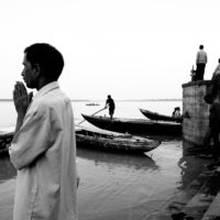 Varanasi, India- A man prays along the shores of the Ganges River. Many believe the river is holy and will bathe themselves in it despite it being terribly polluted.
