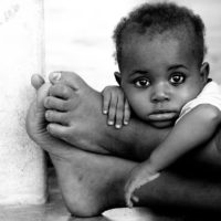 A child waits for medical attention on the feet of her mother at the Nungwi Beach clinic in Zanzibar, Tanzania by travel photographer Kira Horvath.