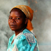 Santhe, Malawi- Portrait of a woman in her smoke filled kitchen in Santhe, Malawi by travel photographer Kira Horvath.