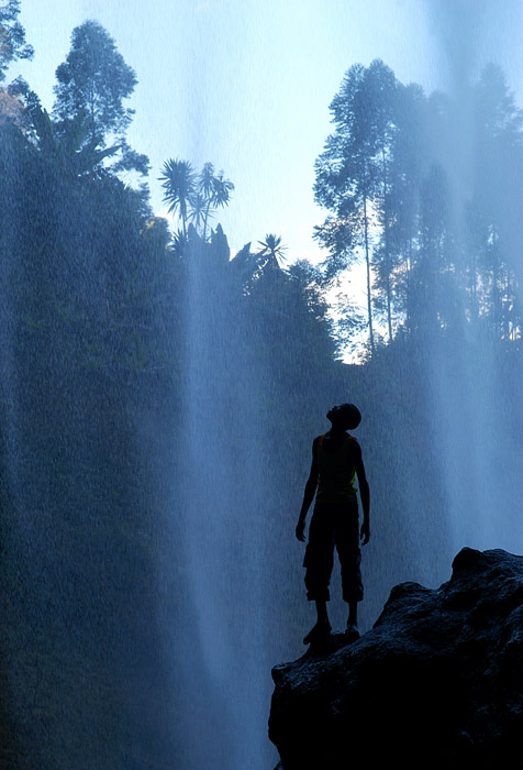 Boy standing under Sipi Falls in Uganda Africa by travel photographer Kira Vos (Horvath).