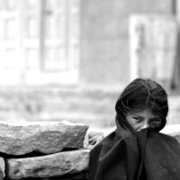 Lake Titicaca, Peru- A girl covers her face and watches other children play on Taquile Island.