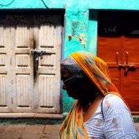 Varanasi, India- A woman walks passed one of the many brightly painted alleyways of the holy city of Varanasi.