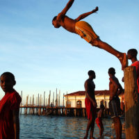 Zanzibar, Tanzania- Boys jump from a pier in Stone Town as the sun sets on this exotic island. Stone Town, is a World Heritage Site and is claimed to be the only functioning ancient town in East Africa. Zanzibar's main industries are spices, raffia, and tourism.