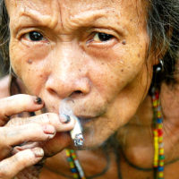 Mentawai Island, Indonesia- A woman smokes a rolled up cigarette while taking a break from foraging for food. The Mentawai live in the remote jungles of the small Indonesian island and are known for their heavily tattooed bodies and sharpened teeth.