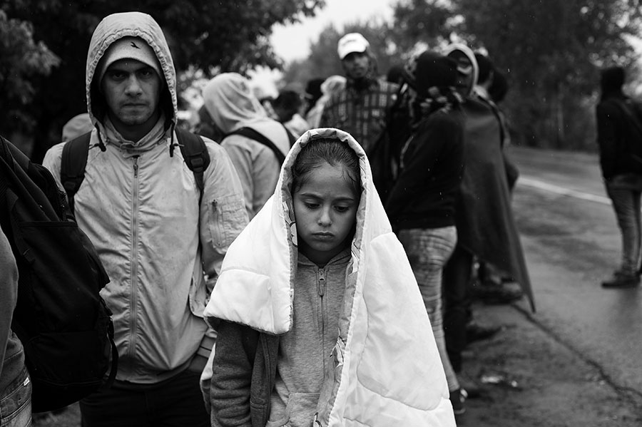 A syrian girl tries to stay dry as she waits for a bus in Serbia.  - Kira Horvath Photography