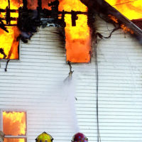 NAPOLEON, MI.,- A fire raged through a house in Napoleon Wednesday as Leoni firefighters tried in vein to maintain the blaze.