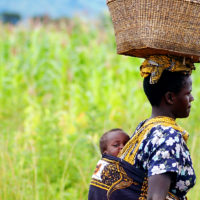 Livingston, Zambia- A woman carries a basket of food on her head and her baby strapped to her back in Livingston, Zambia.