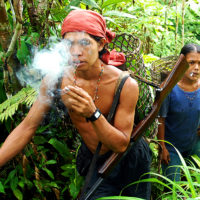 Mentawai Island, Indonesia- A family of jungle dwellers searches for fruit near their hut on Mentawai Island, Sumatra. The Mentawaian men often hunt wild pigs, deer and primates while the women and children gather wild yams and other wild food.