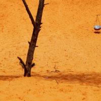 Mui Ne, Vietnam- A woman carries baskets of food through the red sand dunes of Mui Ne, Vietnam.