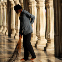 Amritsar, India- A man sweeps a hallway in the early morning light at the Golden Temple in Amritsar, India.