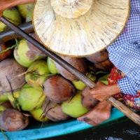 Bangkok, Thailand- A man, with a canoe full of coconuts for sale, paddles through Bangkok's Damnoen Saduak market in Thailand.