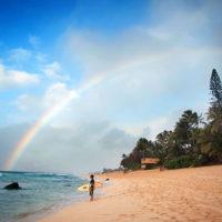 Banzai Beach, Hawaii- A surfer watches the waves under a fresh rainbow on the North Shore.