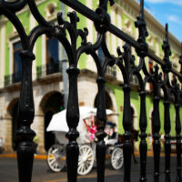 Merida, Mexico- A horse drawn carriage rides down the colorful streets of the colonial city Merida, Mexico.