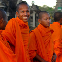 Angkor Wat, Cambodia- Buddhist monks in crimson robes gather at the entrance to the temple zone.