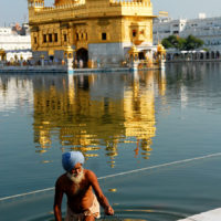 Amritsar, India- A man walks out of the water after bathing himself in the holy waters near the Golden Temple of Amritsar.