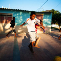 Boys play soccer on the colorful streets of the small fishing village of Tagana, Colombia