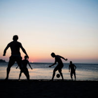 Men play soccer at sunset on the beach of Tagana, Colombia