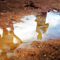 Embu, Kenya- Members of Kenya's Men's National Cross Country team are reflected in a puddle while training around Moi Stadium's dirt track in Embu, Kenya on Tuesday, March 14, 2006. Thirty-eight of Kenya's best cross country runners attended the Embu camp to prepare for the upcoming World Championships in Japan on April 1st and 2nd.