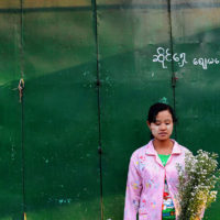 Girl sells flowers at a market in Yangon, Myanmar