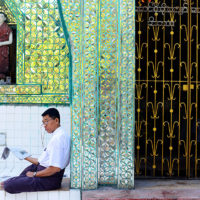 Man reading a newspaper next to a temple in Yangon, Myanmar