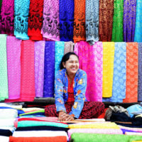 Woman selling brightly colored cloth in a market in Yangon, Myanmar