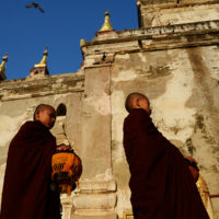 Bagan, Myanmar- Young moms line up and wait for their morning almes during sunrise at the Gawdaw Palin Buddhist Temple.