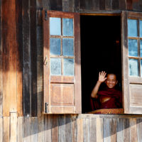 Monk waving from a wooden monastery in Teetain, Myanmar