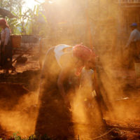 Teetain, Myanmar- A woman rakes the red dirt in front of her thatched home in Teetain, a typical Pao Village. Teetain is the last overnight stay on the popular three day trek from Kalaw to Inle Lake.