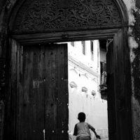 a boy runs through the ornate doors in Stonetown, Zanzibar