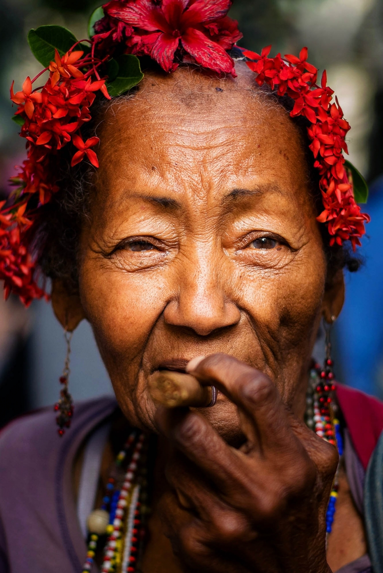A woman with flowers in her hair chews on a cigar while walking down the streets of old town Havana, Cuba. Cuba stock photography by Kira Vos.