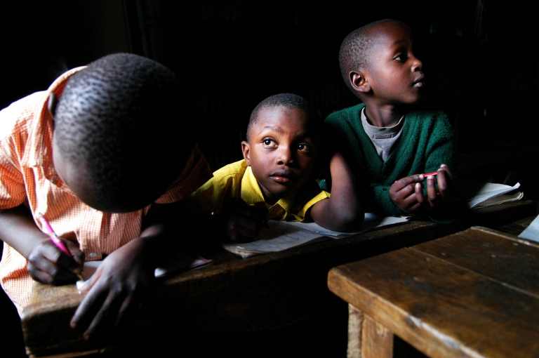 A boy stares out the window while taking a break from his English alphabet exercises at the Kitui Village Community Nursery School in the Majengo Slums of Nairobi, Kenya. Started by the Foundation for Orphaned Children, registered in 2005, the school acts as both daycare and school to the children who attend. The goal of this organization is to provide basic needs to the children such as food, clothing, education, shelter and health care. They are currently soliciting donations to provide these basic needs. Africa stock photography by Colorado photographer Kira Vos.