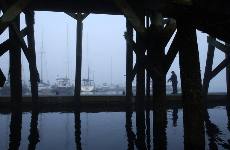 New England Fisherman fishing by the Beverly, MA harbor on a cold day by travel photographer Kira Vos (Horvath).