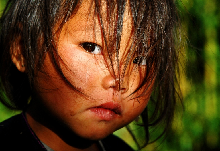 Photo at sunset of sad girl from Hmong tribe in Sapa Vietnam by travel photographer Kira Vos (Horvath).