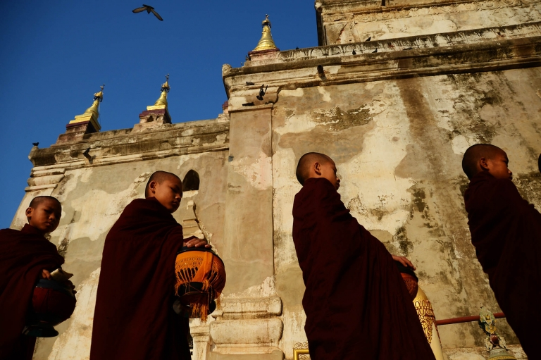 Young monks line up and wait for their morning alms during sunrise at the Gawdaw Palin Buddhist Temple. Myanmar stock photography by Kira Vos.